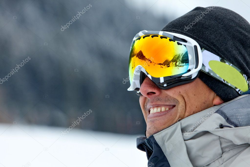 Skier smiling and wearing ski glasses in the mountains — Stock Photo #7740625