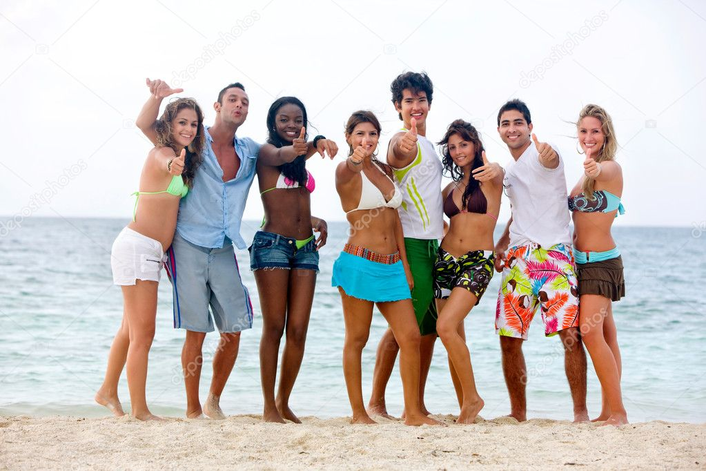 Happy group of at the beach with thumbs up — Stock Photo #7741415