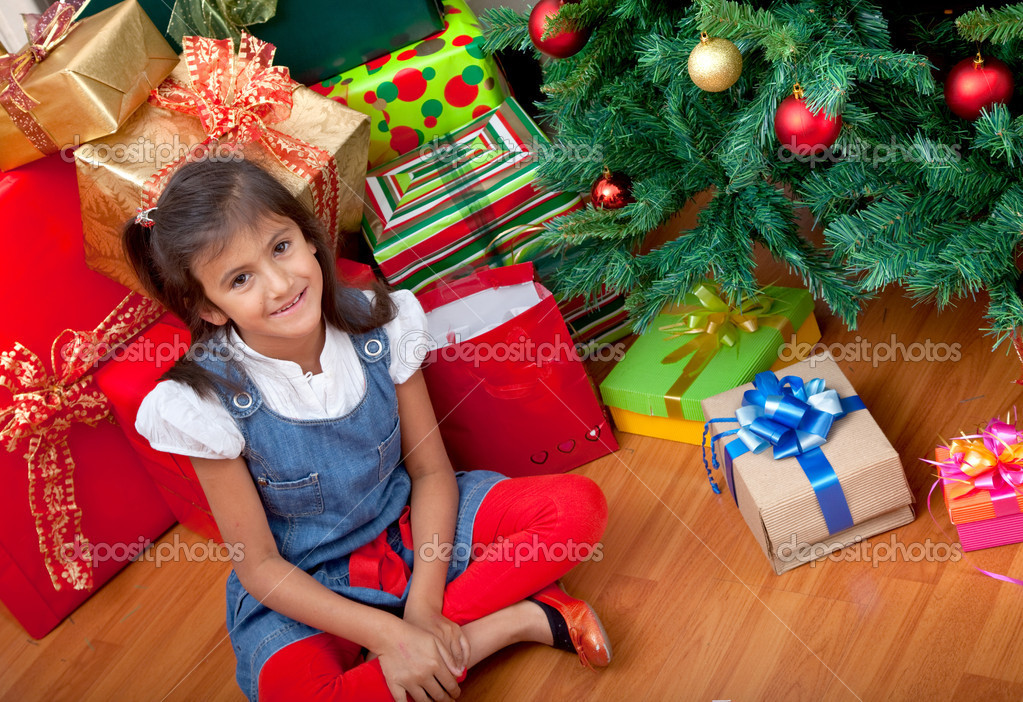 Happy girl next to a Christmas tree surrounded by gifts — Stock Photo #7741534
