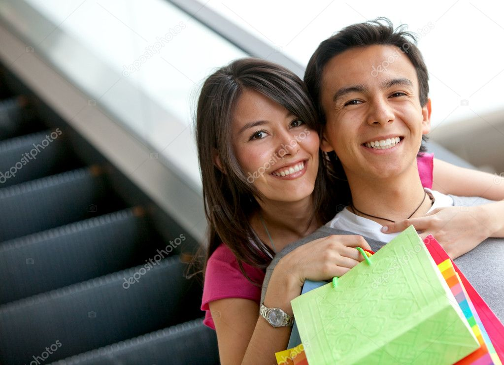 Happy couple at a shopping center with bags  Stock Photo #7745992