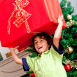 Boy carrying a christmas present - Stock Photo