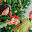 Christmas woman giving a present — Stock Photo