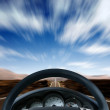 Steering wheel on a highway - Stock Photo