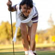 Woman placing a golf ball - Stock Photo