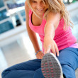 Woman at the gym stretching — Stock Photo