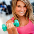 Gym woman lifting free weights — Stockfoto