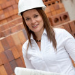 Stock Photo: Female engineer with blueprints