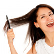 Woman combing her hair - Stock Photo