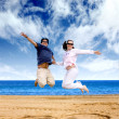 Beach couple having fun - jumping — Stock Photo