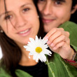 Cute couple with a white flower — Stock Photo