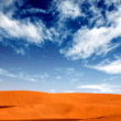 Sand dunes landscape with a blue sky — Stock Photo