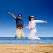 Stock Photo: Beach couple jumping of joy