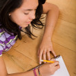 Casual girl writing on a notepad on the floor — Stock Photo