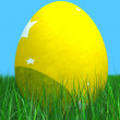Easter egg in yellow on the grass - Stock Photo