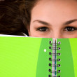 Beautiful female student peeping over a green notebook — Stock Photo