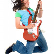 Teenage girl jumping with an electric guitar - Stock Photo