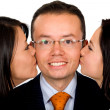 Business man being kissed by partners - Stock Photo