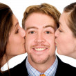 Business man with two girls kissing him — Stock Photo