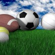 Sports balls on grass - horizontal - Stock Photo
