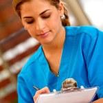 Female doctor writing — Stock Photo