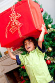 Boy carrying a christmas present — Stock Photo