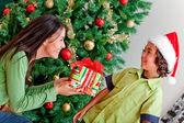 Christmas woman giving a present — Stock Photo