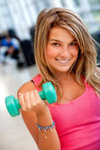 Gym woman lifting free weights — Stock Photo