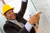 Male architect pointing at blueprints — Stock Photo
