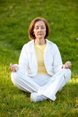 Woman practicing yoga outdoors — Stock Photo