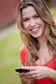 Woman texting on the phone — Stockfoto