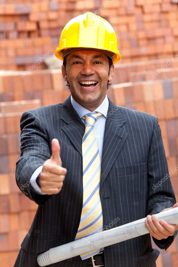 Happy engineer holding a model in a construction with his thumb up — Stock Photo #7751583