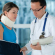 Stock Photo: Injured womwith doctor