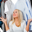 Overwhelmed woman with clothes — Stock Photo