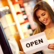 Woman opening a retail store - Stock Photo