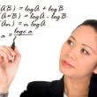 Asian girl solving a mathematical formula - Stock Photo
