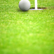 Golf ball close to hole - Stock Photo