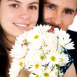 Couple smiling with flowers — Stock Photo