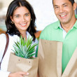 Happy couple shopping in supermarket with bags — Stock Photo