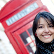 Woman outside a telephone booth - Stock Photo