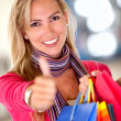 Shopping woman with thumbs up — Stockfoto