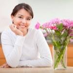 Beautiful woman next to flowers — Stock Photo #7769629