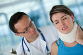 Injured woman with a physiotherapist — Stock Photo