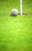 Golf ball close to hole — Zdjęcie stockowe