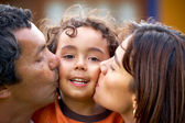 Parents kissing their son — Stock Photo
