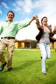 Happy couple running outdoors — Stock Photo