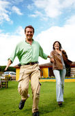 Happy couple running outdoors — Stock Photo