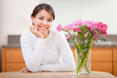 Beautiful woman next to flowers — Stock Photo