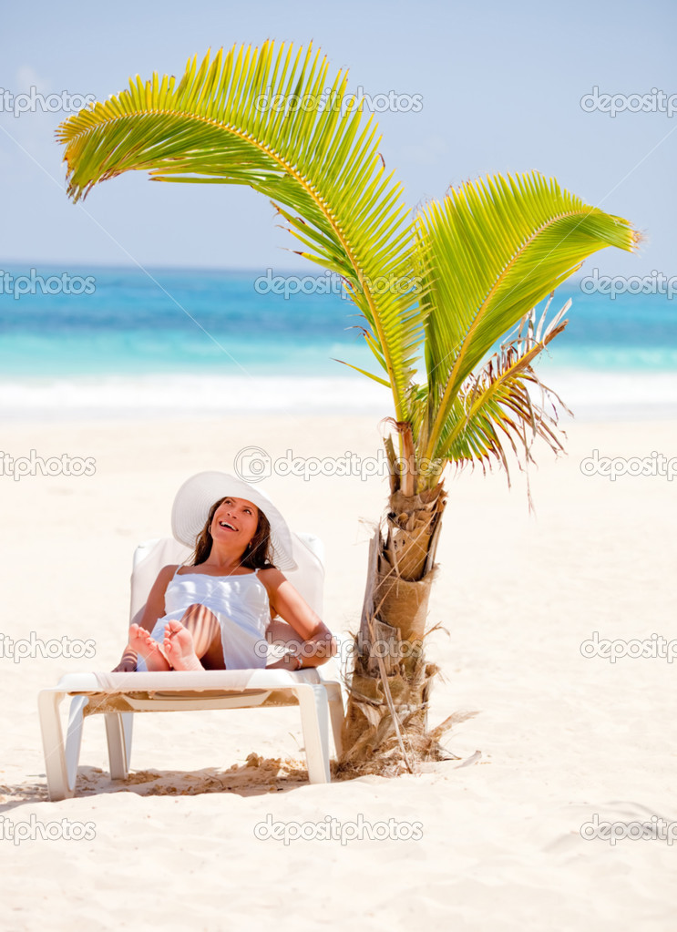 Happy woman lying at the beach under the shadow of a palm tree — Stock Photo #7764459
