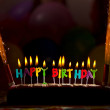 Happy birthday candles on cake - Stock Photo
