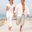 Beach couple running — Stockfoto